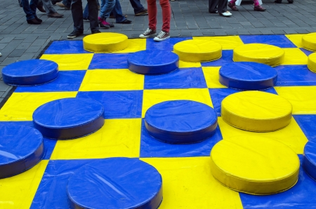 yellow and blue huge checkers figures outdoor and many people legs  people fun entertainment play object in street