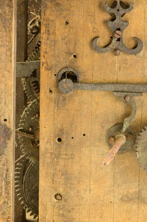 residue: Retro wooden grunge clock box and mechanism gear wheel residue closeup  Stock Photo