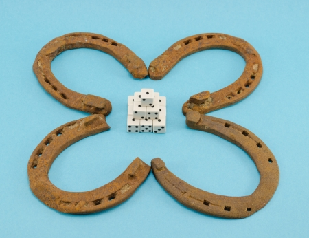 clover made of rusty retro horse shoes and gamble dices on blue background  Luck talisman   Stock Photo - 16469355