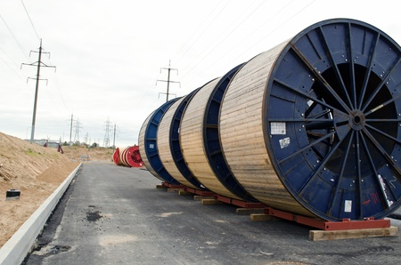 high voltage cable reels in front of power line construction site  road building work and electricity line laying underground   Stock Photo