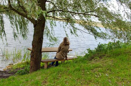 young blond woman sit on wooden bench under willow tree branches and admire lake landscape.