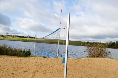 closeup of volleyball court sand and net on autumn lake shore   photo