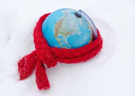mother earth: red scarf on earth globe sphere in winter snow snowbank  care of mother earth concept