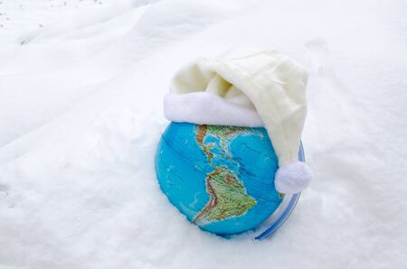 earth globe sphere in winter snow snowbank and white cap hat on it concept   photo