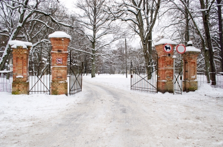 ancient open red brick gates to park and dog car prohibition signs in winter   photo