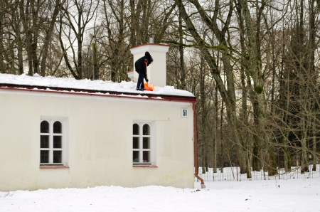 man in black with orange plastic shovel tool clean snow from roof in winter   photo