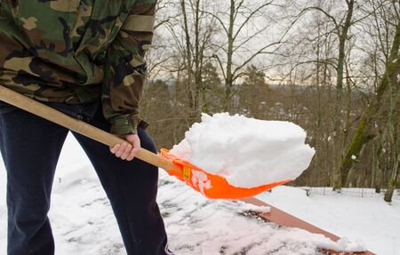 closeup man in camouflage with orange plastic shovel tool clean snow from roof in winter