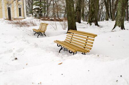 snowdrifts: empty yellow park benches between winter snowdrifts snow in park