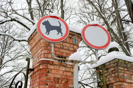 sign prohibiting walk out dogs and drive cars on park red brick gates covered with snow in winter. Stock Photo - 17292195