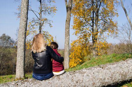 bewonderen: blonde vrouw moeder zit op gebroken boomstam met haar dochter te bewonderen herfst prachtige bomen.