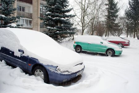 blizzard snow fall on car standing in block flat house outdoor parking.  photo