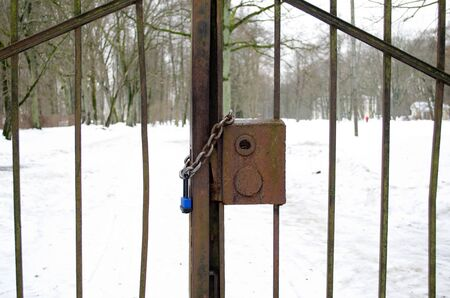 closeup of chain and lock closed retro rusty steel park gates in winter. Stock Photo - 17448466