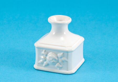 small white retro ceramic vase dish decoration with ornaments on blue background.  photo
