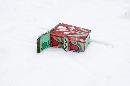 colorful painted bird nesting box lie fallen on snow in winter   photo