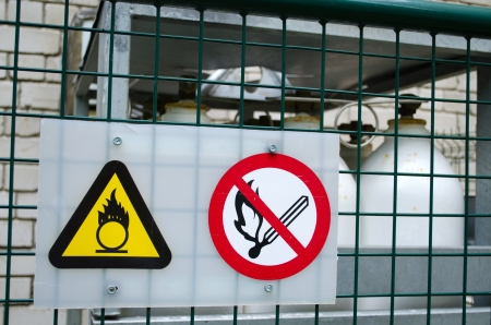 fire warning signs symbol near compressed oxygen gas cylinders. dangerous objects.  Stock Photo