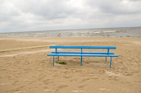 blue bench on sea ocean seaside beach sand in cloudy day.  photo