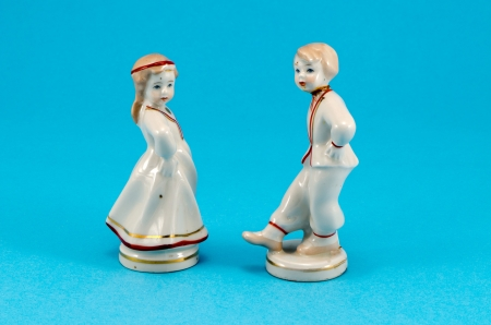 two ceramic toy decor dancers statue boy and girl on blue background.  photo