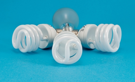 novel new modern fluorescent lights and old incandescent heat bulb on blue background  economic technology for less electricity energy consumption Stock Photo - 17710987