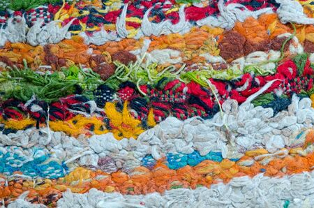 retro colorful grunge dirty carpet rug mat made of wool thread background closeup
