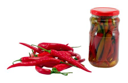 ecological red hot chilli pepper paprika preserved canned in glass pot surrounded by natural ones healhy food resource for winter time