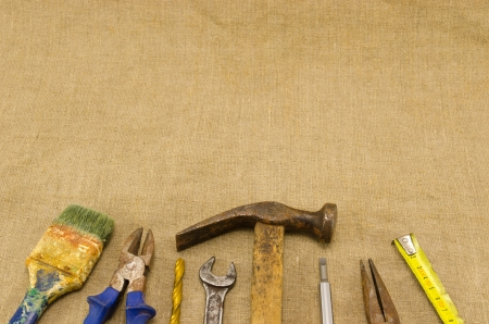 different retro rusty construction work tools hammer meter chisel wrench pincers screwdriver brush bit on linen cloth cloth background.  photo