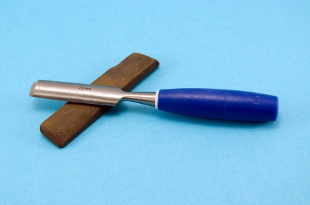 chisel graver carve tool for wood work and whetstone stone on blue background.  Stock Photo