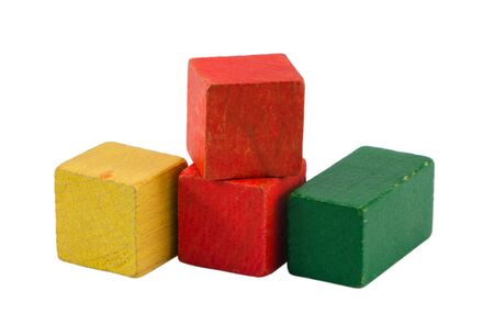 composition of yellow red green wooden vintage log toy brick constructions isolated on white background  Stock Photo