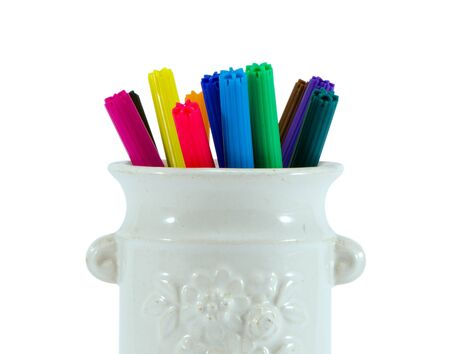 closeup of colorful felt tip pens in retro clay cup isolated on white background  photo