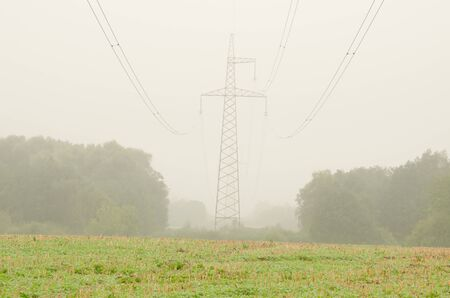 view of agriculture field and high voltage electricity pole wire in morning fog