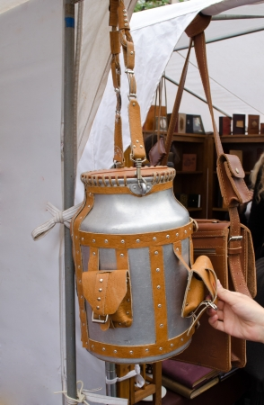 churn upholstered in brown leather straps, pockets and long handle with rivets