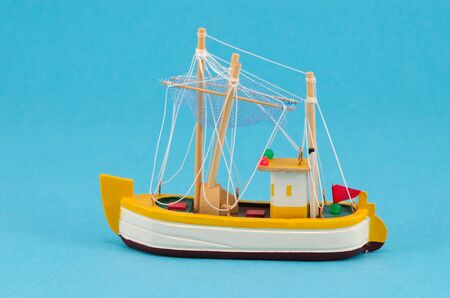 wooden handmade object boat ship with sail model decoration on blue background   photo