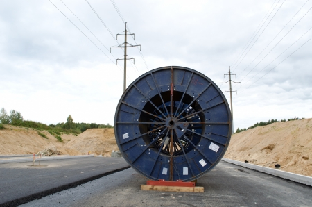 huge high voltage cable reels power line construction site  road building work and electricity line laying underground