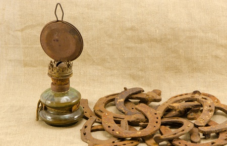 rusty retro kerosene lamp and horse shoes on linen cloth cloth material background  photo