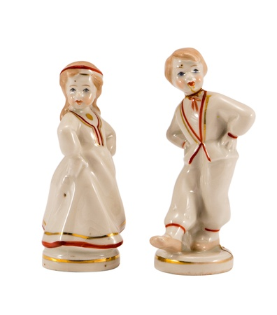 two ceramic toy decor dancers statue boy and girl isolated on white background photo
