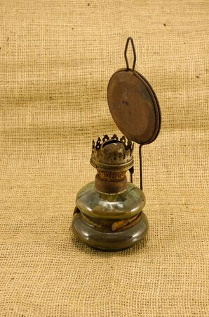 paraffine: roestige retro petroleumlamp op jute landelijke achtergrond