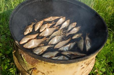 closeup of ecologic salted fish smoke in smokehouse smoke house made of old rusty barrel
