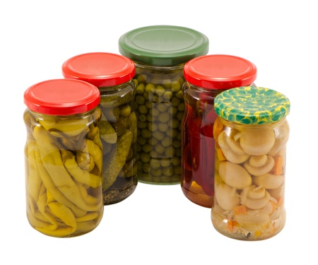 mushroom peppers  cucumbers tomatoes and pease preserved in glass pots jars isolated on white background ecological natural food resource for winter   photo