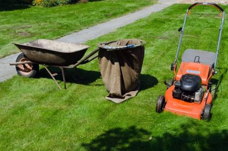 ready for operation mower and wheelbarrow to throw the grass  Zdjęcie Seryjne