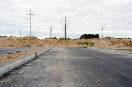 voltage gray: building highway asphalt road construction site  high voltage electricity line   Stock Photo