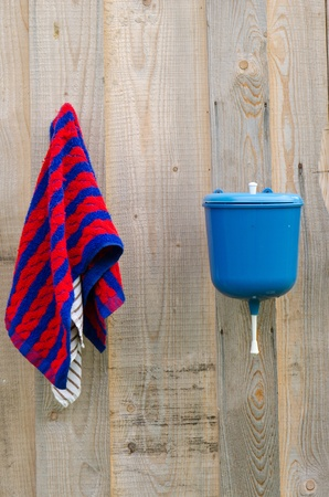 lavabo: rural plastic hand wash tool and towel hang on wooden wall   Stock Photo