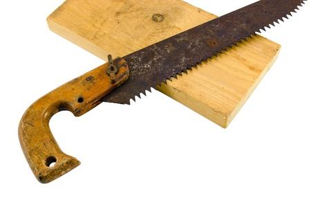 serrucho: retro mano corte transversal sierra oxidada herramienta de sierra de mano y parte de la tabla de madera aisladas sobre fondo blanco
