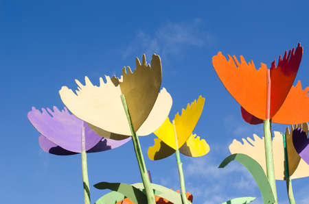 colorful stylized design decor tulips cut from plywood wood board against blue sky background   photo