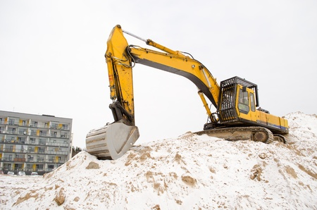 sand quarry: excavator stand on quarry sand pit pile soil covered with snow and new modern apartment house in winter  construction industry works