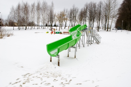 outdoor water park slide on frozen snowy lake in winter playground   photo