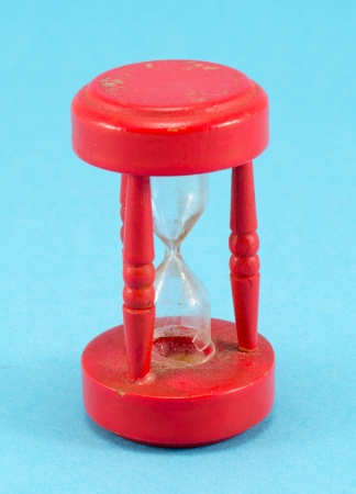 broken red retro object sand glass clock on blue background   photo
