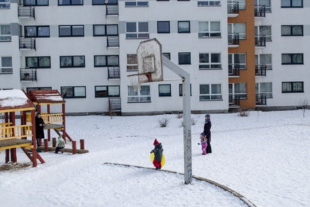 VILNIUS, LITHUANIA - FEBRUARY 26: childrens backyard basketball court in the winter small children with nannies on February 26, 2013 in Vilnius.
