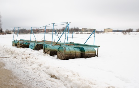 quay dock made of old steel barrels covered with snow wait for warm season on frozen lake shore in winter.