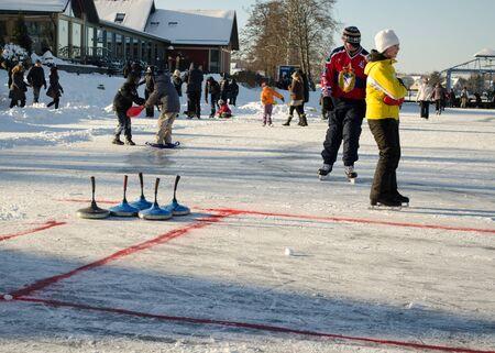 TRAKAI, LITHUANIA - CIRCA JANUARY 2013 - people play winter game curling eisstock and slide skating kit frozen ice on circa January 2013 in Trakai   Stock Photo - 19710818