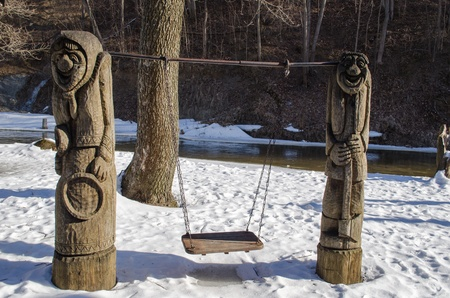 carved wooden rural craft design empty swing on snow covered river bank and water flow in winter   photo