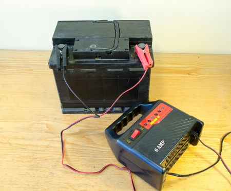 12v: auto battery charger clamps connected to car accumulator at home.